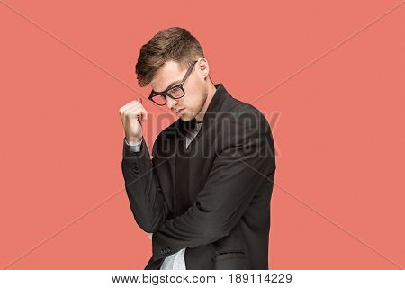 Young pondering handsome man in black suit and glasses isolated on red studio background