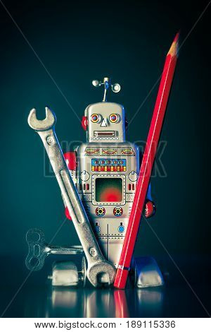 A toy robot holds a wrench and a red pen