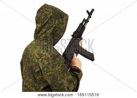 The person keeps the AK-47 assault rifle in the green camouflage form a back to the camera