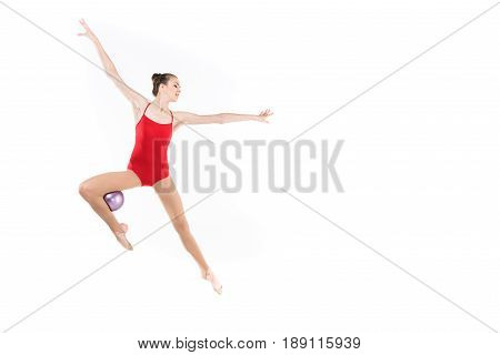 Young Caucasian Woman Rhythmic Gymnast Jumping With Ball And Looking Away