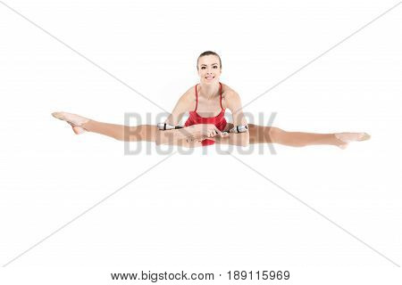 Young Woman Rhythmic Gymnast Jumping With Clubs And Looking At Camera