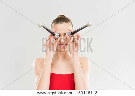 Young Smiling Caucasian Woman Rhythmic Gymnast Holding Clubs In Front Of Eyes