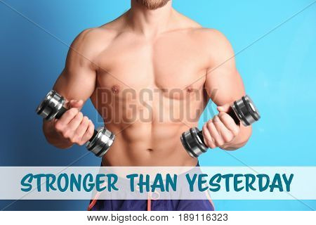 Sport motivation concept. Text STRONGER THAN YESTERDAY and muscular man with dumbbells on color background