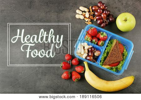 Text HEALTHY FOOD, different products and lunchbox on gray background