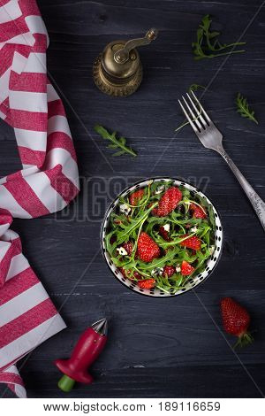 Homemade fresh salad with arugula, strawberries and cheese roquefort on a wooden background. Low key. Top view