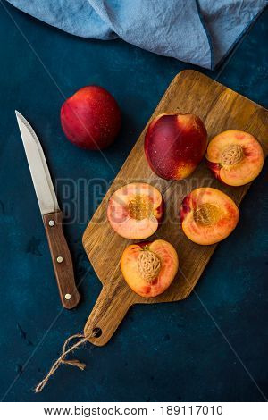 Ripe juicy nectarines cut in half whole on wood cutting board knife dark blue background top view flat lay clean minimalist style
