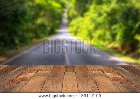 Brown wood table and blurry road runs through forest in background. Empty table for display product.