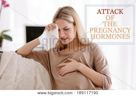 Pregnant young woman suffering from headache at home. Text ATTACK OF THE PREGNANCY HORMONES