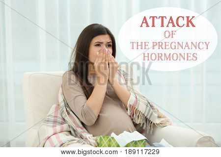 Pregnant young woman sitting in armchair and crying. Text ATTACK OF THE PREGNANCY HORMONES