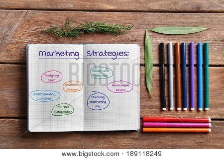 Notebook with scheme of MARKETING STRATEGIES and felt-tip pens on wooden background