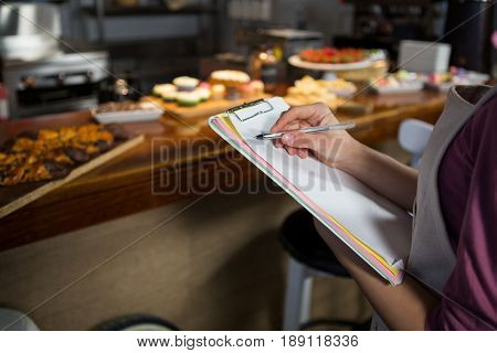 Mid-section of staff maintaining records on clipboard in market