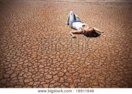 Young woman lying in the middle of a desert.