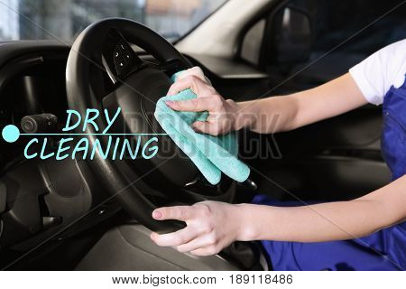 Woman with rag cleaning steering wheel. Concept of dry clean