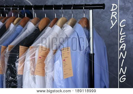 Concept of dry cleaning service. Hangers with clean clothes and receipts hanging on rack