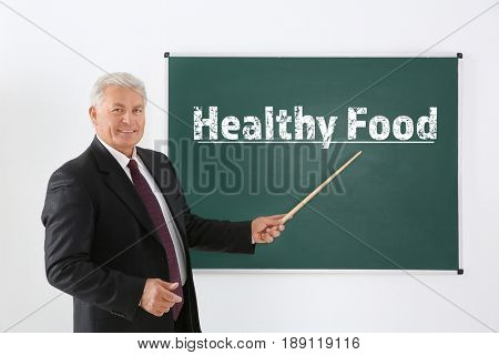 Senior teacher with pointer near blackboard on white background. Text HEALTHY FOOD on chalkboard
