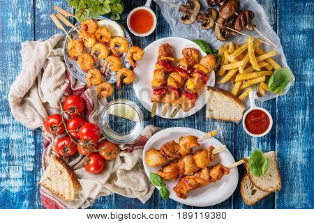 Variety of BBQ snack lunch. Plates grilled spicy prawn kebabs, chicken, pork, vegetables, mushrooms skewers, bread, french fries potatoes with sauces and greens over blue wooden background. Flat lay