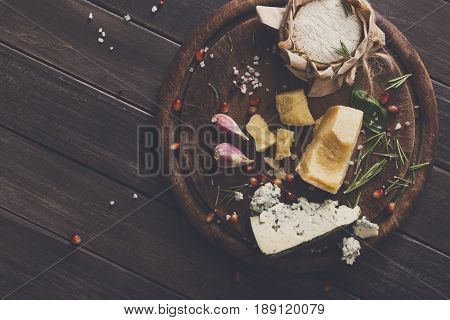 Cheese delikatessen top view on rustic wood. Wooden round desk with blue cheese roquefort, parmesan, camembert and brie cuts decorated with garlic, pomegranate and basil, french cuisine ingredients