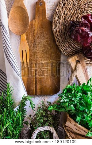 Provence style kitchen interior white wooden wall cutting board utensils rattan coaster linen towel fresh garden herbs rosemary thyme parsley spring summer atmosphere
