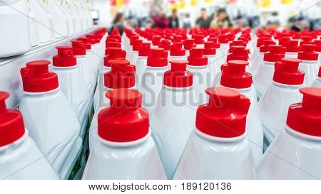 White plastic bottles with red lids in a row. Background.