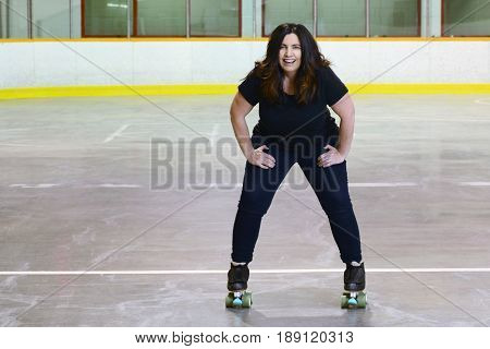 happy woman quad roller skating in roller rink