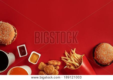 Two hamburgers and french fries, sauces and drinks on red background. Fast food. Hamburger with chicken nuggets. Top view, flat lay with copyspace.