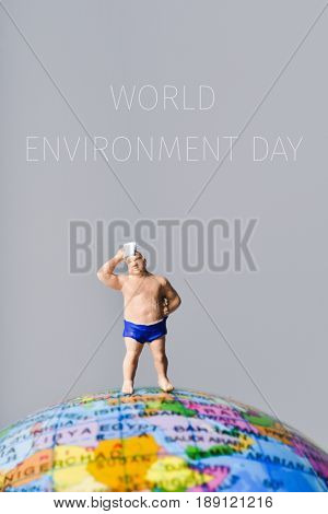 miniature man wearing swimsuit and drying his forehead with a handkerchief on the top of the terrestrial globe and the text world environment day
