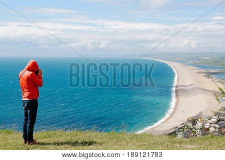 Young man in jeans and red jacket takes photos of Weymouth and coastline from a viewing platform on the Isle of Portland, Dorset, UK.