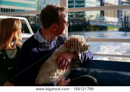 LONDON, UK - MAY 22, 2017: Couple with a dog on the lap watch sunset from the deck of Thames Clippers, part of Transport for London network.