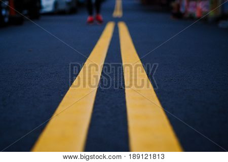 Yellow road line on black street, texture and background