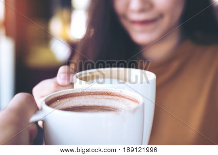 Close up image of man and woman clink coffee mugs in cafe