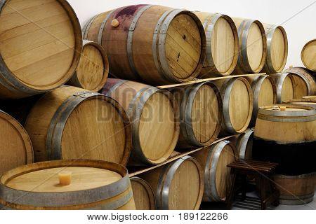 Pile of wine wooden barrels in winery