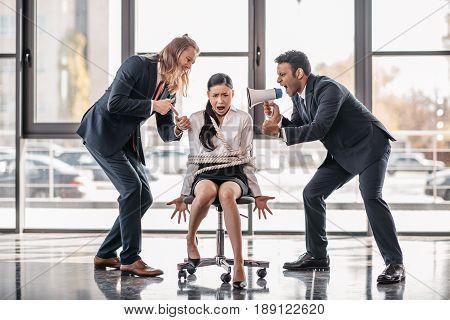Yelling Asian Businesswoman Bound With Rope On Chair While Businessmen Screaming On Her With Megapho