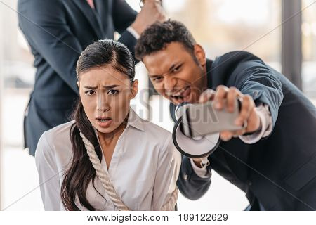 Asian Businesswoman Bound With Rope While Businessman Taking Selfie And Screaming In Megaphone