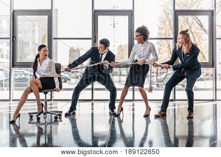Asian Businesswoman Bound With Rope On Chair And Multicultural Business Team Pulling Her, Team Spiri