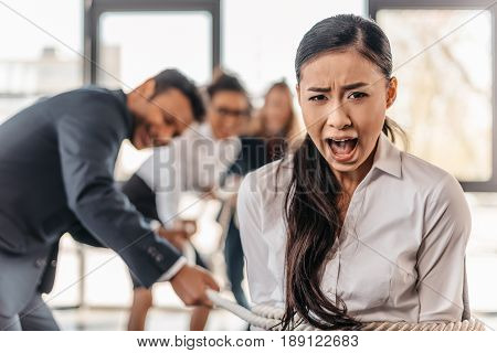 Yelling Asian Businesswoman Bound With Rope And Businesspeople Pulling Her, Team Spirit Business Con