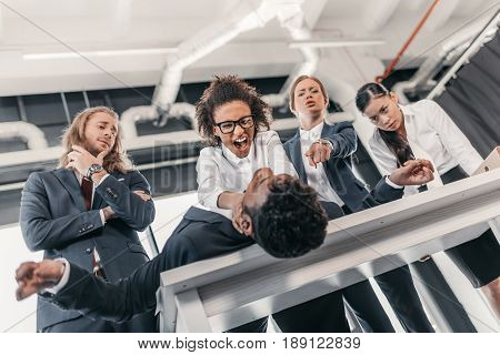 Three Young Angry Businesswomen Punishing Businessman Lying On Table, Business Team Meeting Concept