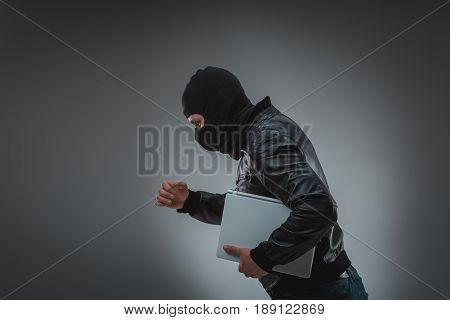 Thief stealing a laptop computer. Isolated on gray background. Studio shot