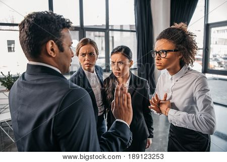 young emotional businesspeople in formalwear quarrelling at modern office business team meeting