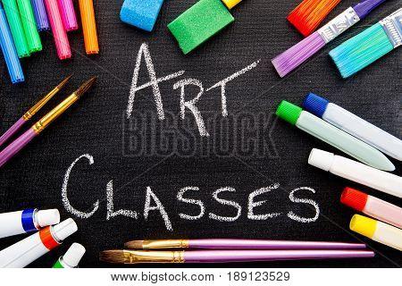 Art Classes handwritten on chalkboard with art equipment