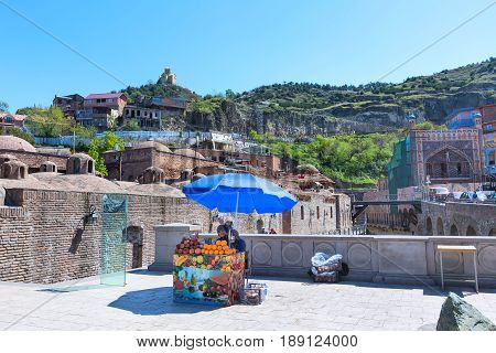 Tbilisi, Georgia - April 24, 2017: Sulphur baths and fresh orange and pomegranate juice sellers in Old Town of Tbilisi