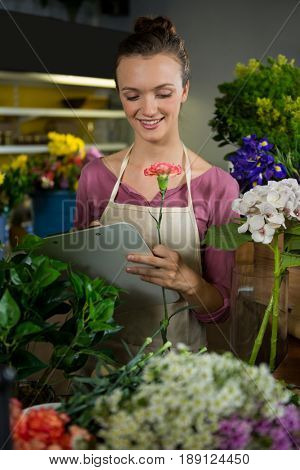 Female florist maintaining record on clipboard in flower shop