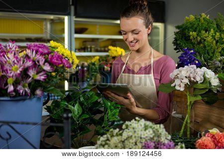 Happy female florist using digital tablet in florist shop