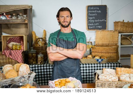 Portrait of staff standing with arms crossed at counter in bakery shop