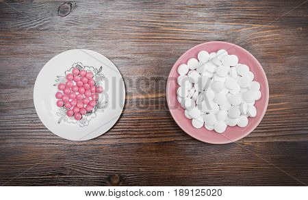 Bright pink pills on a white saucer and big white pills on a pink saucer on a wooden dark background