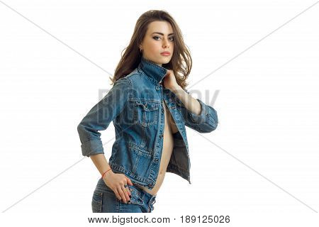 Portrait of a chic brunette that stands with unfastened denim jacket and looking forward is isolated on a white background