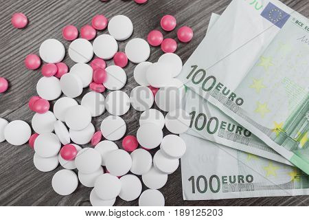 Many round white and pink tablets lie next to three money bills of one hundred euros on a brown wooden background