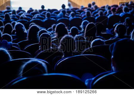 People, children, adults, parents in the theater watching the performance. People in the auditorium looking at the stage. Shooting from the back