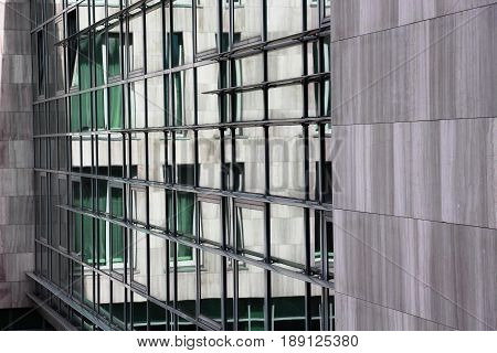 Reflection of windows in city windows. Gray wall.