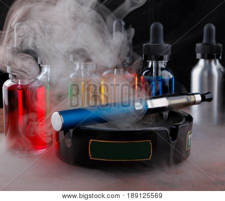 Electronic cigarette on the ashtray and vape liquids within vapor on granite surface. Black background.