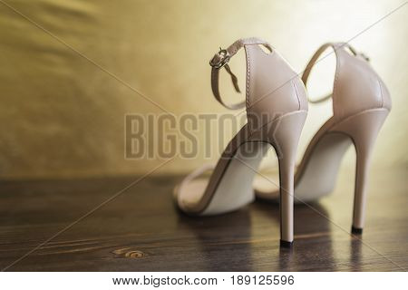 Beige open sandals with thin straps on high heels stand on a dark wooden floor against a background of a golden wall a rear view.
